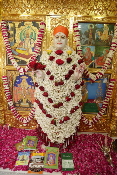 Divine darshan of Jeevanpran Shree Muktajeevan Swamibapa adorned in garments made entirely of bright white flowers trimmed with large deep red roses