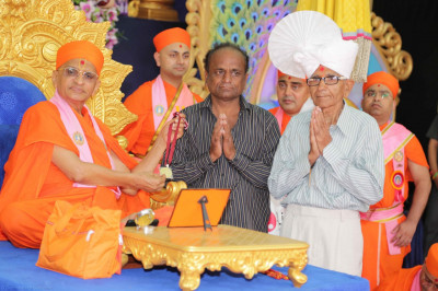 His Divine Holiness Acharya Swamishree presents gold medals