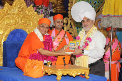 His Divine Holiness Acharya Swamishree presents publications and prasad as well as a prasad paag and shawl to honoured guests