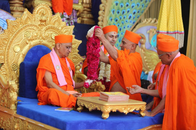 Sants offer poojan and present His Divine Holiness Acharya Swamishree with a garland of fresh flowers