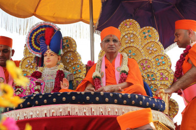 Divine darshan of Lord Shree Swaminarayan and His Divine Holiness Acharya Swamishree seated on a magnificent golden chariot
