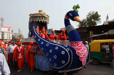 A blue float shaped like a peacock glides majestically through the street procession