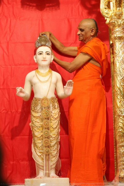 His Divine Holiness Acharya Swamishree bathes Lord Shree Swaminarayan in luke warm water