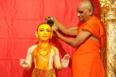 His Divine Holiness Acharya Swamishree bathes Lord Shree Swaminarayan in luke warm saffron water