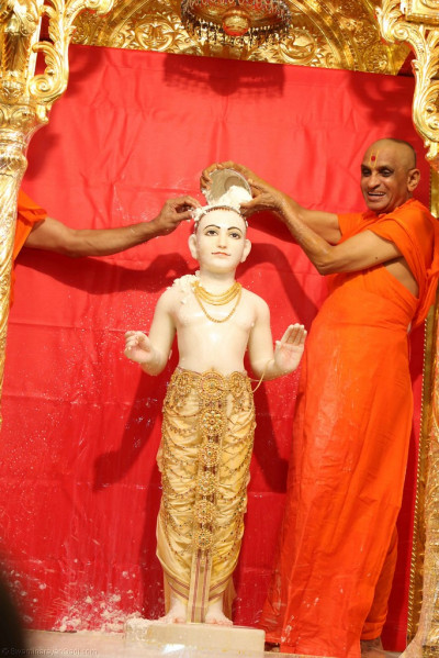 Acharya Swamishree bathes Lord Shree Swaminarayan in fine sugar