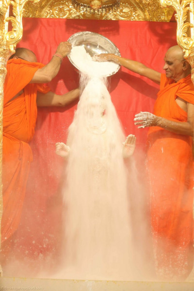 Acharya Swamishree bathes Lord Shree Swaminarayan in powdered sugar