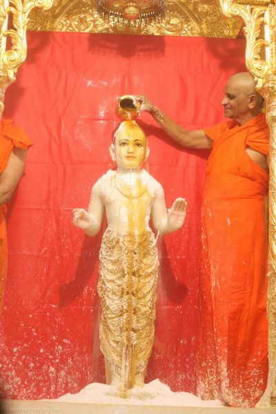 Acharya Swamishree bathes Lord Shree Swaminarayan in luke warm saffron water