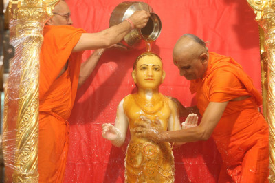 Acharya Swamishree bathes Lord Shree Swaminarayan in thick sweet honey