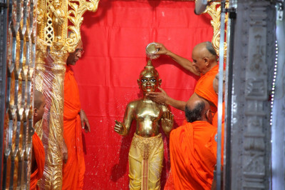 Acharya Swamishree bathes Shree Harikrishna Maharaj in luke warm water