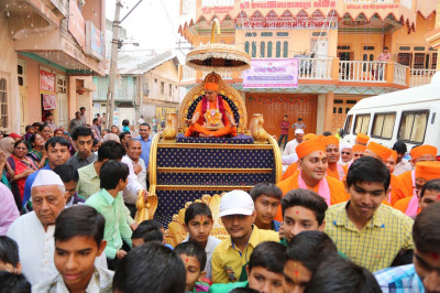 Acharya Swamishree gives darshan during a procession in Mokhasan on the first day of Rajat Mahotsav