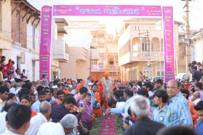 Acharya Swamishree walks along the path flanked by disciples