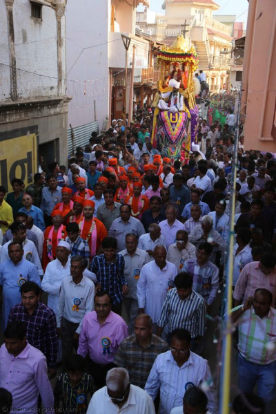 The procession continues through the narrow streets
