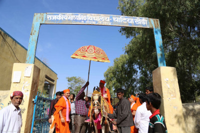 Acharya Swamishree rides a horse during a procession from the school