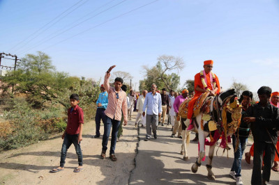Acharya Swamishree rides a horse during a procession