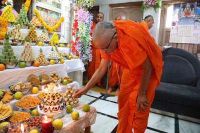 A celebrations cake is cut by Acharya Swamishree