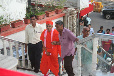 Disciples escort His Divine Holiness Acharya Swamishree up the stairs to the mandir level