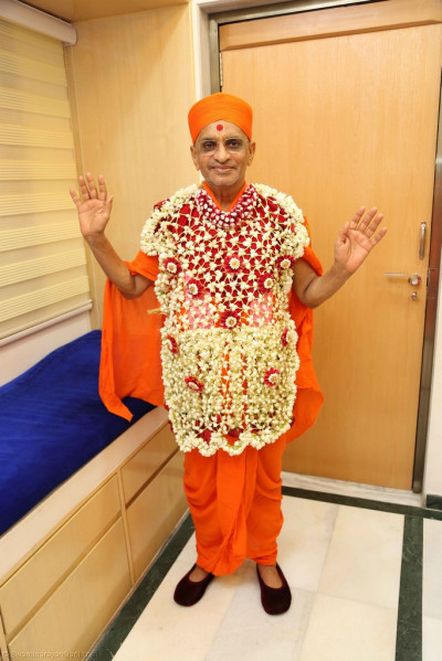 Divine darshan of His Divine Holiness Acharya Swamishree adorned in a shawl of fresh of fragrant flowers
