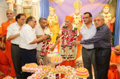 Disciples offer various garlands of fresh fragrant flowers to His Divine Holiness Acharya Swamishree