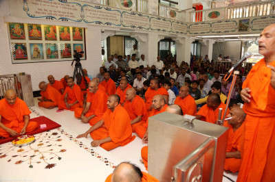 Sants melodiously chant the divine names of Lord Shree Swaminarayan during the poojan ceremony