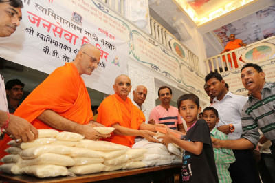 His Divine Holiness Acharya Swamishree and sants ditribute grain and exercise books to the very needy young children