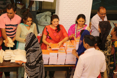 Disciples ditribute grain and exercise books to the very needy young children