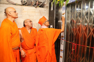 Acharya Swamishree Maharaj consecrates one of the elevators of the building