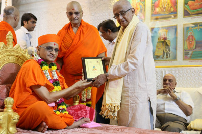 Former judge of the Bombay High Court Shree Hosbet Suresh receives a memento from Acharya Swamishree Maharaj