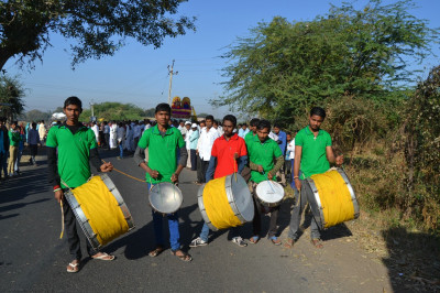 Disciples play large metal drums as part of the procession