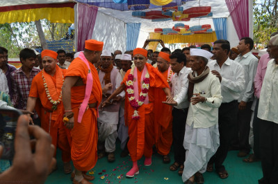 Disciples escort His Divine Holiness Acharya Swamishree to the grand stage