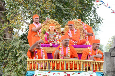 Divine darshan of Acharya Swamishree seated upon a golden throne on the charming float