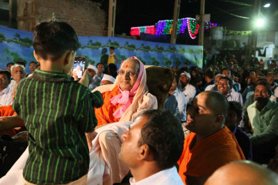 A young disciple takes a photo of Acharya Swamishree Maharaj