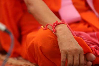 A sacred thread tied on Acharya Swamishree's wrist