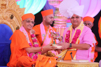 Shree Arvindbhai Patel receives a mememto from Acharya Swamishree