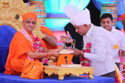 Shree Gopalbhai Govani of the chairty commission receives a mememto from Acharya Swamishree