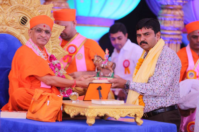 A guest receives a mememto from Acharya Swamishree