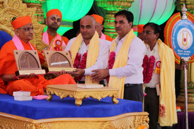 Acharya Swamishree receives a shield from members of the education board