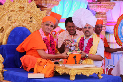 Acharya Swamishree presents a memento to a guest
