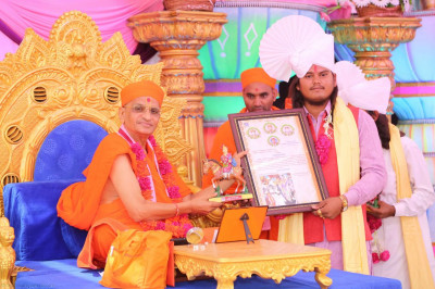 Acharaya Swamishree presents a certificate to the elephant handlers