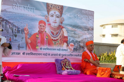 Divine darshan of Shree Harikrishna Maharaj and His Divine Holiness Acharya Swamishree seated on a small beautifully decorated stage on the river bank