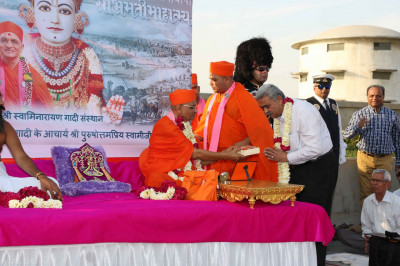 His Divine Holiness Acharya Swamishree presents prasad to honoured guests