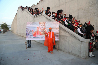 Divine darshan of Acharya Swamishree with members of the pipe band aligning the stairway