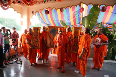 The divine Murtis are carried into the Mandir
