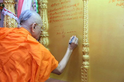 Acharya Swamishree enscribes the sacred name of the Lord in the new singhasan before the Murtis are ceremonially installed