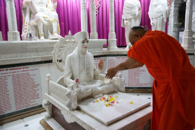 Acharya Swamishree Maharaj showers Jeevanpran Swamibapa with flower petals