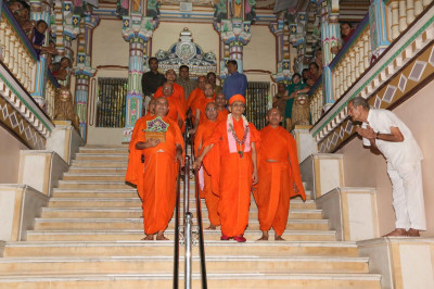 Acharya Swamishree Maharaj walks down the steps of Maninagar Mandir