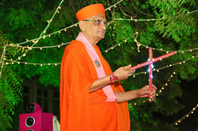 Acharya Swamishree Maharaj plays dandiya during the finale