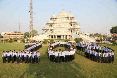 Students and disciples form the number 108 in the grounds of Smruti Mandir