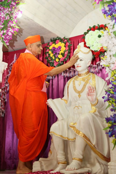 Acharya Swamishree Maharaj impresses a chandlo on Shree Ghanshyam Maharaj