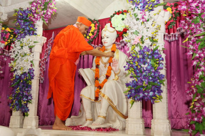 Acharya Swamishree Maharaj puts a garland on Shree Ghanshyam Maharaj