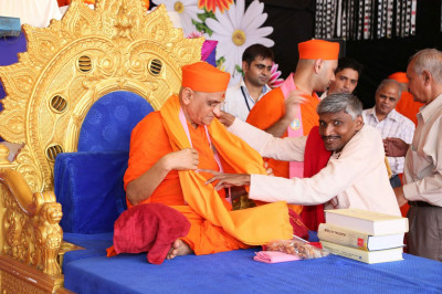 Anilbhai Raval puts a shwal on Acharya Swamishree Maharaj on behalf of Guljar Chhatra Sahyal Samiti